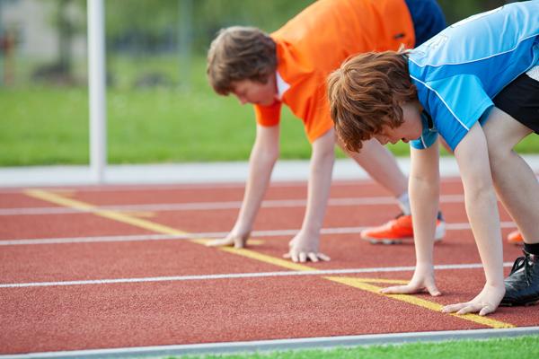 zwei jungen trainieren auf der laufbahn